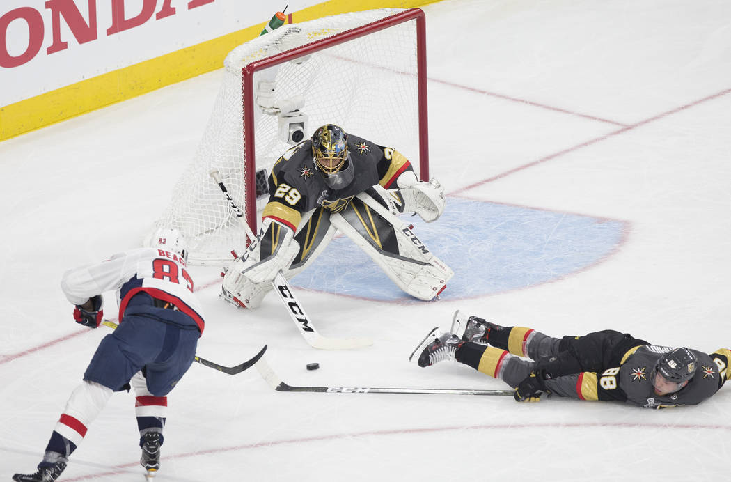 Golden Knights goaltender Marc-Andre Fleury (29) makes a save with the help of defenseman Nate Schmidt (88) against Capitals right wing Jay Beagle (83) in the first period during Vegas' Game 1 mat ...