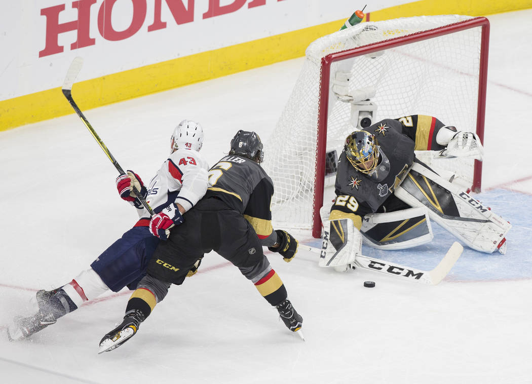 Golden Knights goaltender Marc-Andre Fleury (29) makes a save against Capitals right wing Tom Wilson (43) with the help of defenseman Colin Miller (6) in the first period during Game 1 of the NHL ...