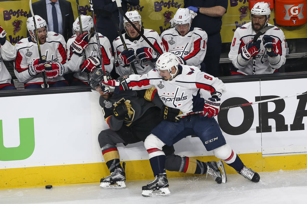 Vegas Golden Knights center Ryan Carpenter (40) gets checked by Washington Capitals defenseman Dmitry Orlov (9) during the first period in Game 1 of the NHL hockey Stanley Cup Finals between the G ...