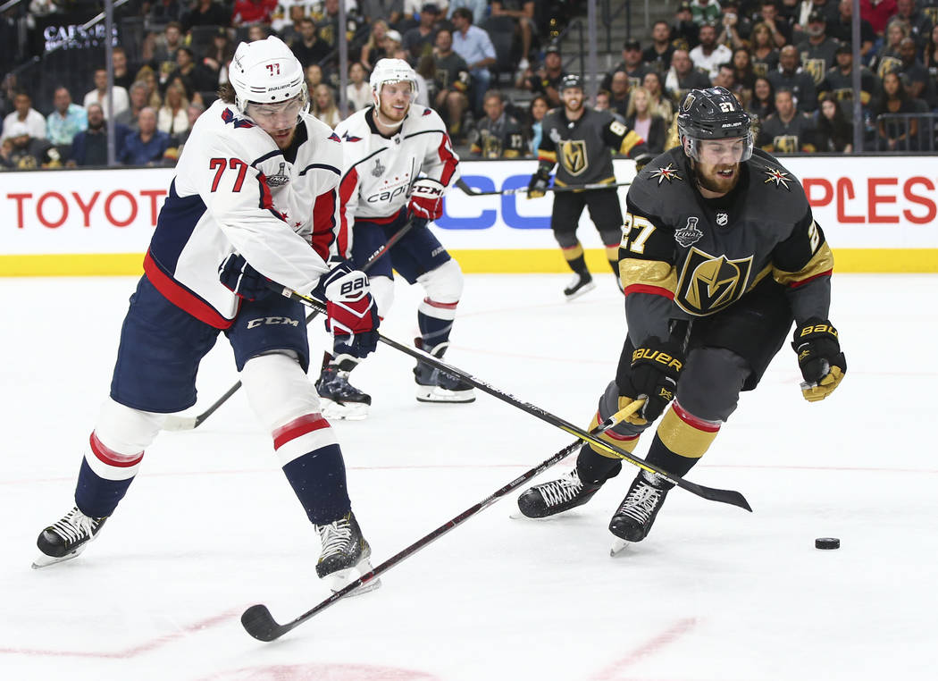Washington Capitals right wing T.J. Oshie (77) sends the puck past Golden Knights defenseman Shea Theodore (27) during the second period of Game 1 of the NHL hockey Stanley Cup Final at the T-Mobi ...