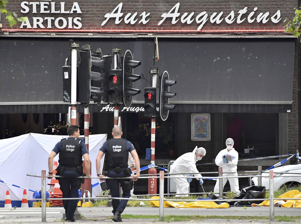 Forensic police, right, investigate at the scene of a shooting in Liege, Belgium, Tuesday, May 29, 2018. A gunman killed three people, including two police officers, in the Belgian city of Liege o ...