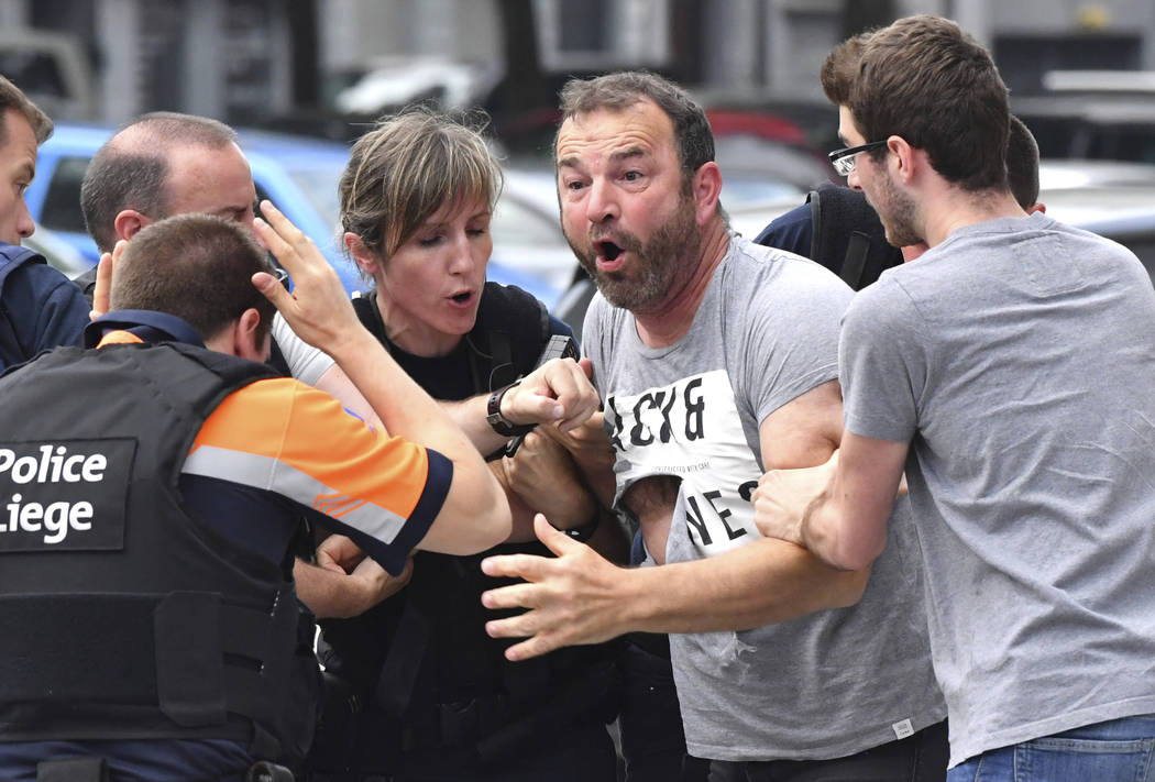 Police try to calm a man who crossed over a police line at the scene of a shooting in Liege, Belgium, Tuesday, May 29, 2018. A gunman killed three people, including two police officers, in the Bel ...