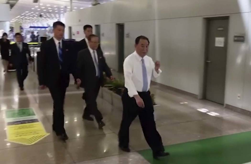 In this image made from video, Kim Yong Chol, in white, a former military intelligence chief who is now Kim Jong Un's top official on inter-Korean relations, walks upon arrival at Beijing airport ...