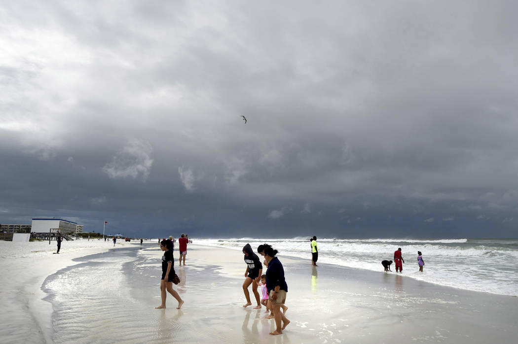 Beachgoers walk on Okaloosa Island in Fort Walton Beach, Fla., Monday, May 28, 2018, as Subtropical Storm Alberto approaches the Gulf Coast. The storm's gusty rain and brisk winds roiled the seas ...