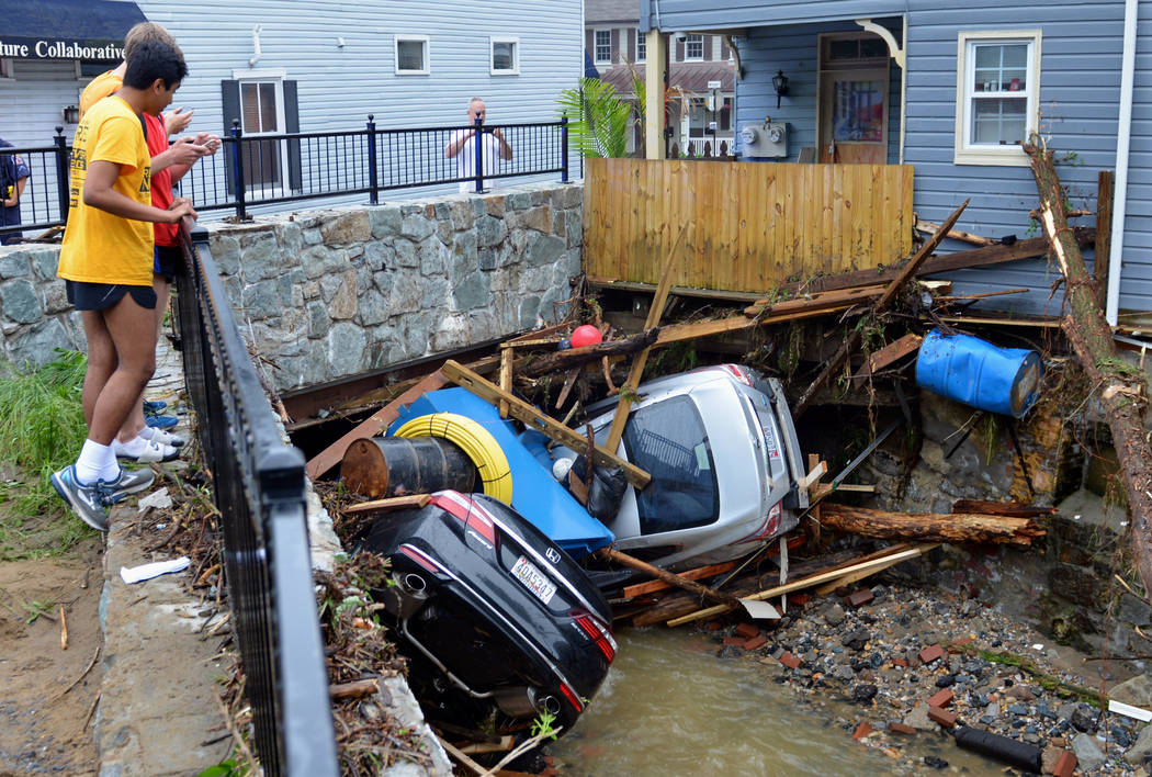 Residents gather by a bridge to look at cars left crumpled in one of the tributaries of the Patapsco River that burst its banks as it channeled through historic Main Street in Ellicott City, Md., ...