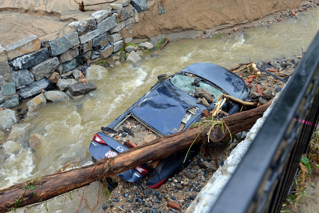 Water moves past a car swept into the riverbank and smashed by a fallen tree is shown just off Main Street in flood-ravaged Ellicott City, Md., Monday, May 28, 2018. Sunday's destructive flooding ...