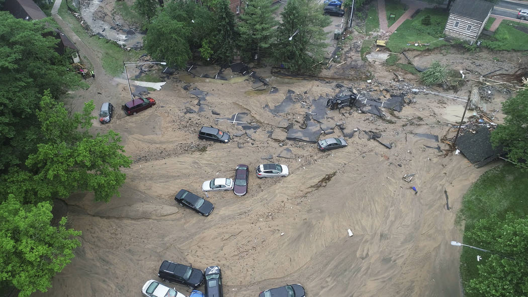 This image made from video provided by DroneBase shows vehicles swept by floodwater near the intersection of Ellicott Mills Drive and Main Street in Ellicott City, Md., Monday, May 28, 2018. Howar ...