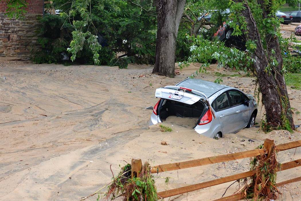 A car that was swept into the riverbank rests just off Main Street in flood-ravaged Ellicott City, Maryland, Monday, May 28, 2018. (David McFadden/AP)