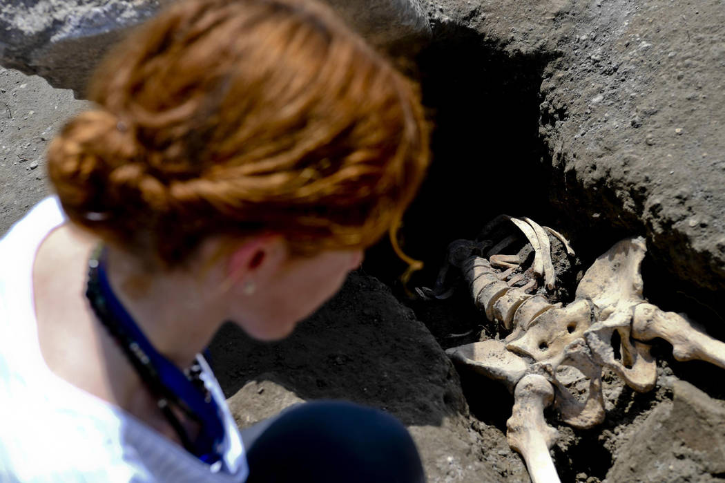 Anthropologist Valeria Amoretti looks at a skeleton of a victim of the eruption of Mt. Vesuvius in A.D. 79, which destroyed the ancient town of Pompeii, at Pompeii' archeological site, near Naples ...