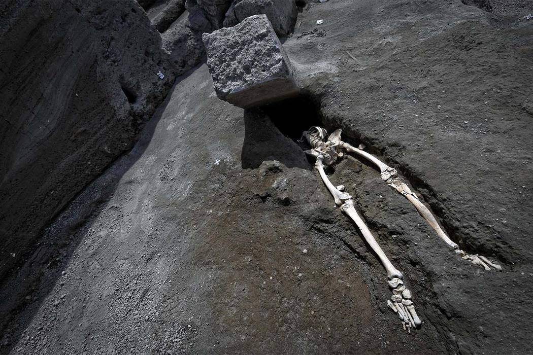 The legs of a skeleton emerge from the ground beneath a large rock believed to have crushed a victim duringh the eruption of Mt. Vesuvius in A.D. 79. (Ciro Fusco/ANSA via AP)
