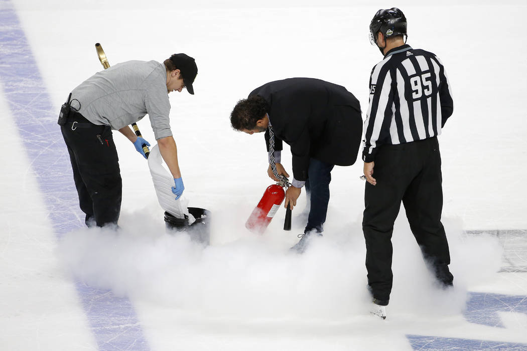 Ice maintenance crew members repair the ice with a fire extinguisher as linesman Jonny Murray watches during the second period in Game 1 of the NHL hockey Stanley Cup Finals between the Vegas Gold ...