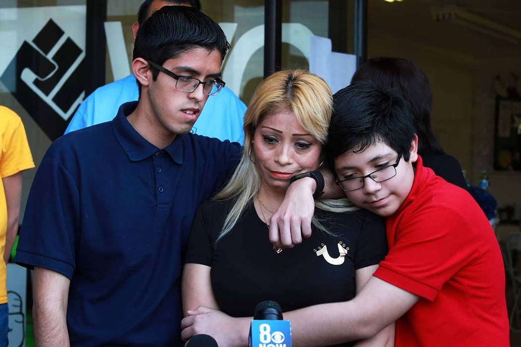 Cecilia Gomez, who was detained by Immigration and Customs Enforcement, is embraced by her sons Ricardo Avelar-Gomez, 18, left, and Eric, 13, after describing her experience with ICE during a news ...