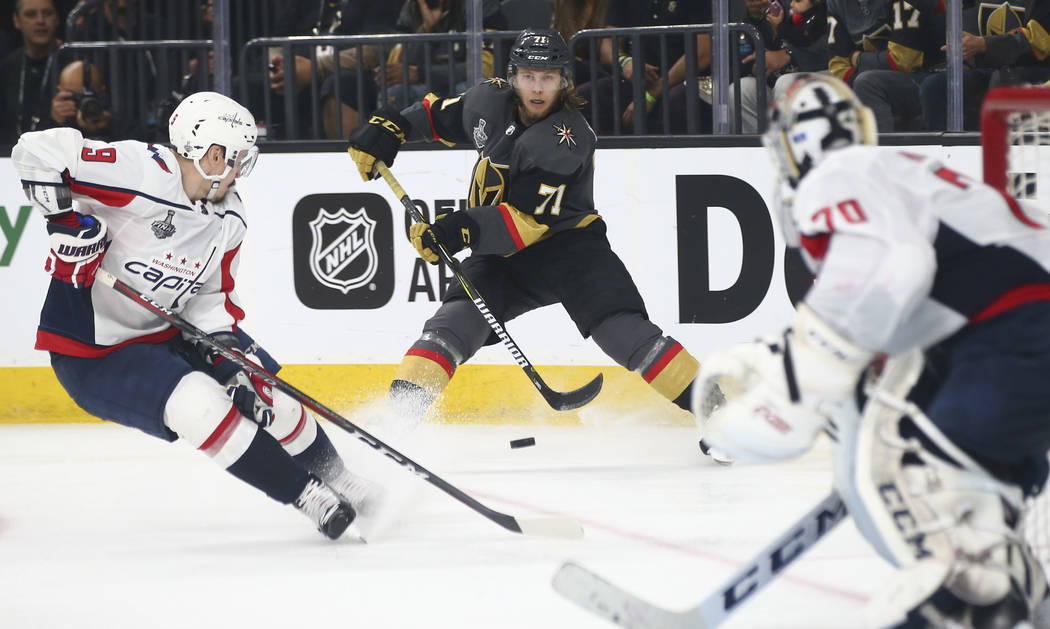 Golden Knights center William Karlsson (71) sends the puck past Washington Capitals defenseman Dmitry Orlov (9) during the third period of Game 1 of the NHL hockey Stanley Cup Final at the T-Mobil ...