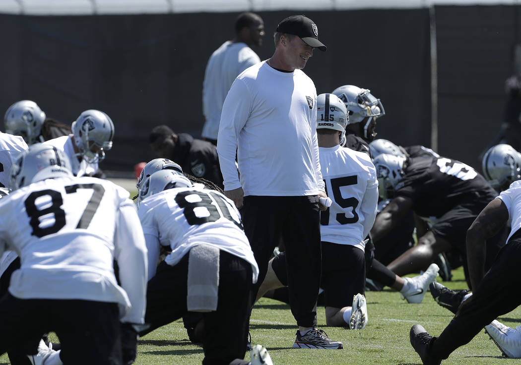 Oakland Raiders head coach Jon Gruden, center, smiles with players during practice at the team's NFL football training facility in Alameda, Calif., Tuesday, May 29, 2018. (AP Photo/Jeff Chiu)