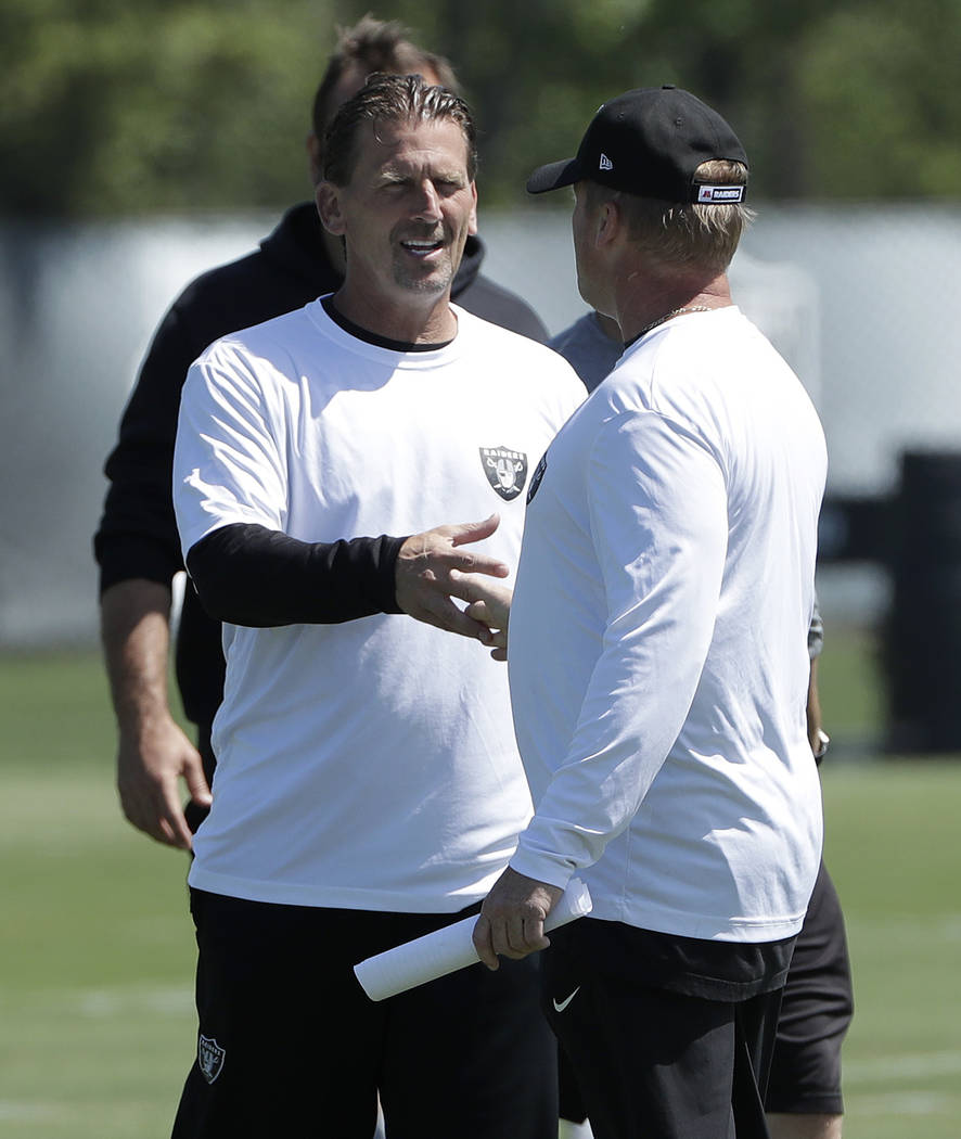 Oakland Raiders offensive coordinator Greg Olson, facing, shakes hands with head coach Jon Gruden during practice at the team's NFL football training facility in Alameda, Calif., Tuesday, May 29, ...