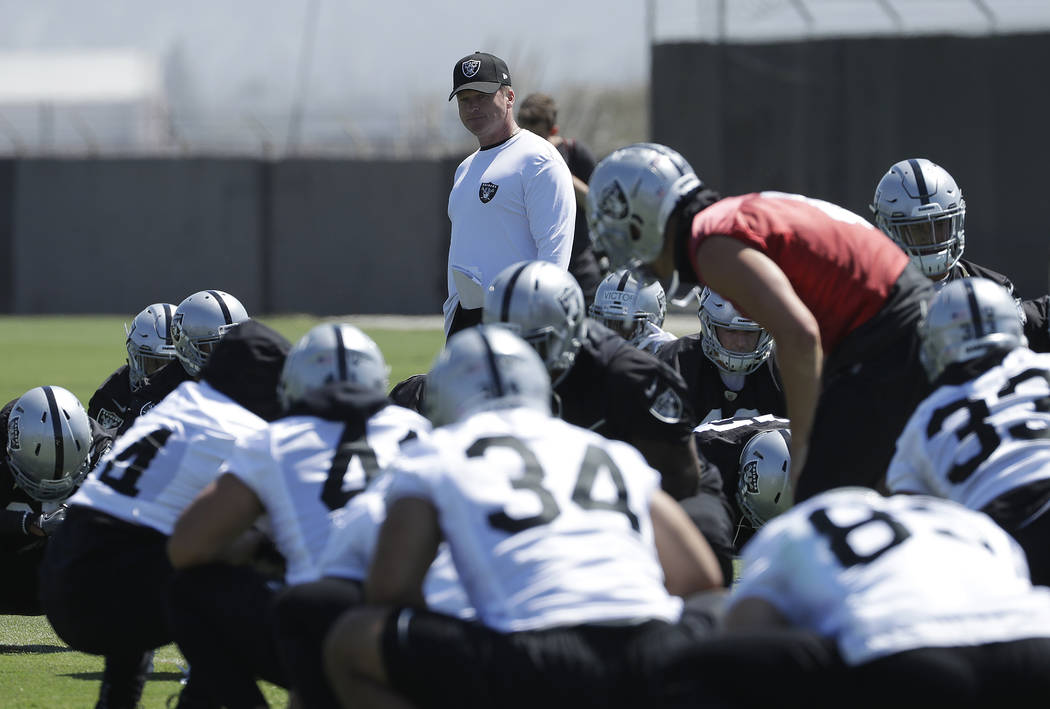 Oakland Raiders head coach Jon Gruden, center, watches as players stretch during practice at the team's NFL football training facility in Alameda, Calif., Tuesday, May 29, 2018. (AP Photo/Jeff Chiu)