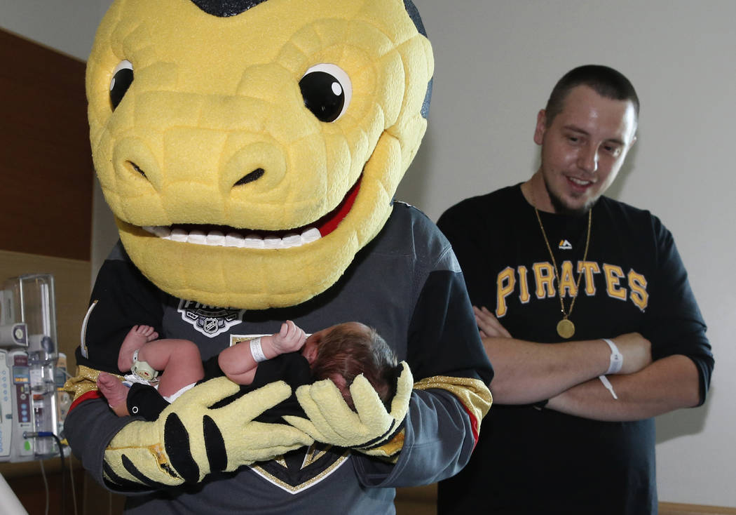 Golden Knights mascot Chance cradles one-day-old Leila Rose as Rose's father Jacob Trautman, right, looks on after Chance delivered Vegas Born onesies to almost 100 newborns at Summerlin Hospital ...