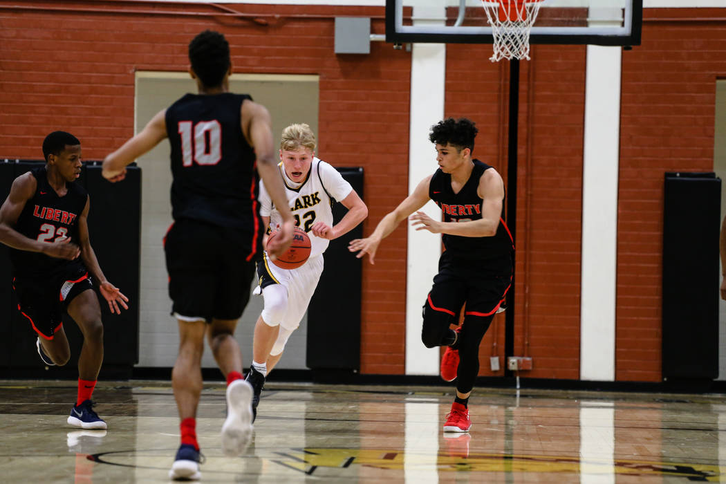 Clark Chargers' Trey Woodbury (22) dribbles the ball past Liberty's players during the second quarter of a basketball game at Ed W. Clark High School in Las Vegas, Friday, Dec. 15, 2017. Clark Cha ...