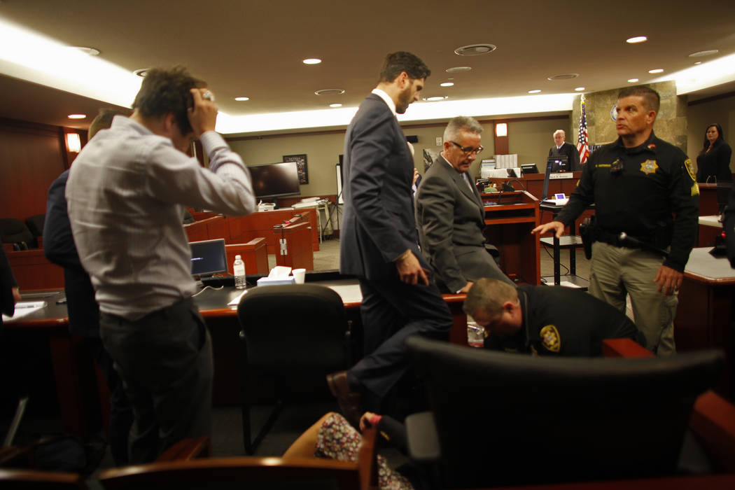 Minh-Han Cox, wife of Gavin Cox, is treated by police and lawyers after collapsing after the verdict for her husband at the Regional Justice Center in Las Vegas, Tuesday, May 29, 2018. Gavin Cox s ...
