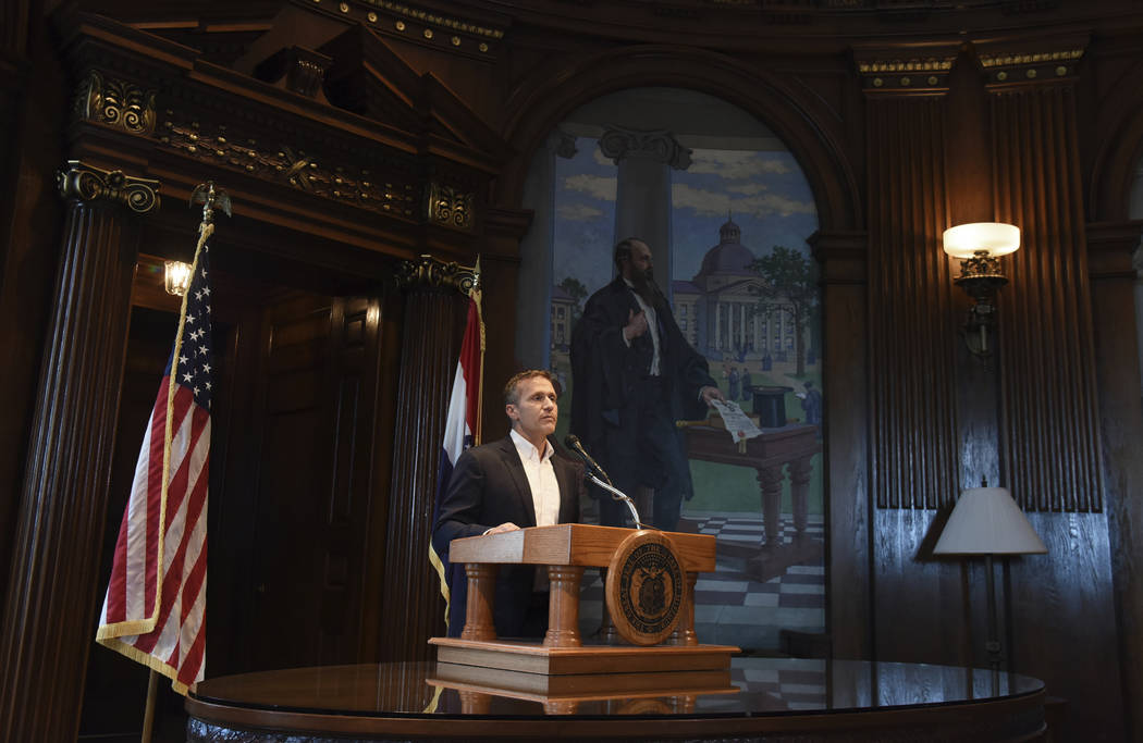 Missouri Gov. Eric Greitens reads from a prepared statement as he announces his resignation during a news conference, Tuesday, May 29, 2018, at the state Capitol, in Jefferson City, Mo. Greitens r ...