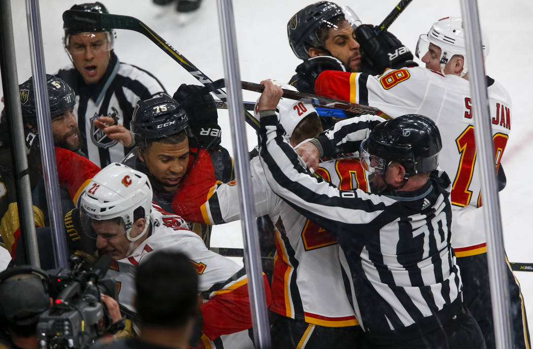 On ice officials break up a fight between the Vegas Golden Knights and the Calgary Flames during the second period of an NHL hockey game at the T-Mobile Arena in Las Vegas on Sunday, March 18, 201 ...