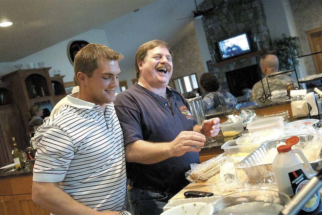 In this April 18, 2006 file photo, Capt. Rick Quashnick, right, shares a laugh with Blake Painter, left, as family and close friends gather at Quashnick's Warrenton, Ore., house to watch the Disco ...