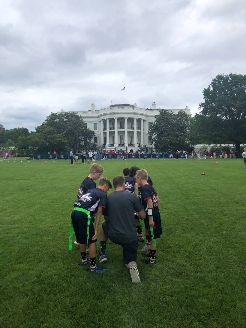 Members of the Las Vegas Patriots flag football team huddle up while playing on the White House lawn on Wednesday, May 30, 2018. Photo by Jason Ahlstrom