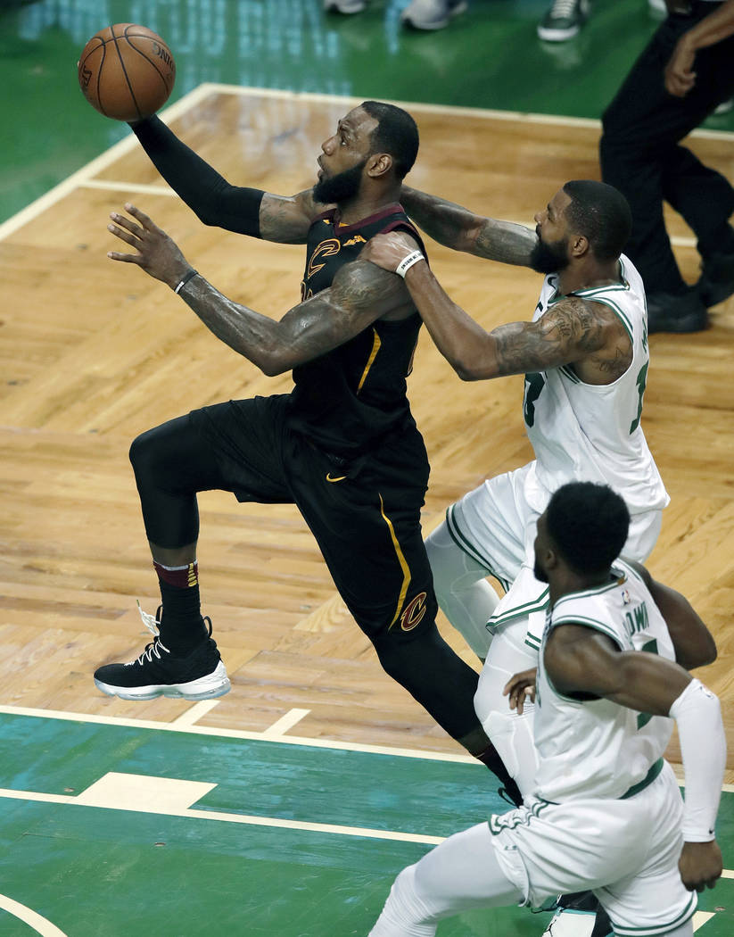 Boston Celtics forward Marcus Morris, right, tries to slow Cleveland Cavaliers forward LeBron James as he drives to the basket during the second half in Game 7 of the NBA basketball Eastern Confer ...