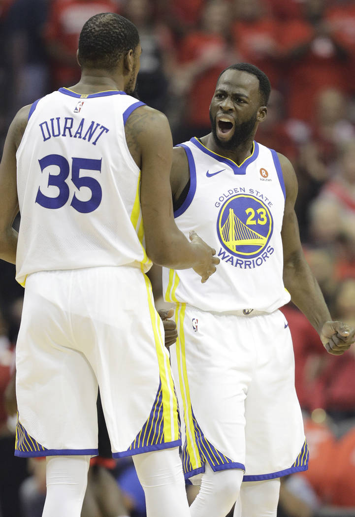 Golden State Warriors forward Draymond Green (23) celebrates a play with teammate Kevin Durant (35) during the first half in Game 7 of the NBA basketball Western Conference finals against the Hous ...