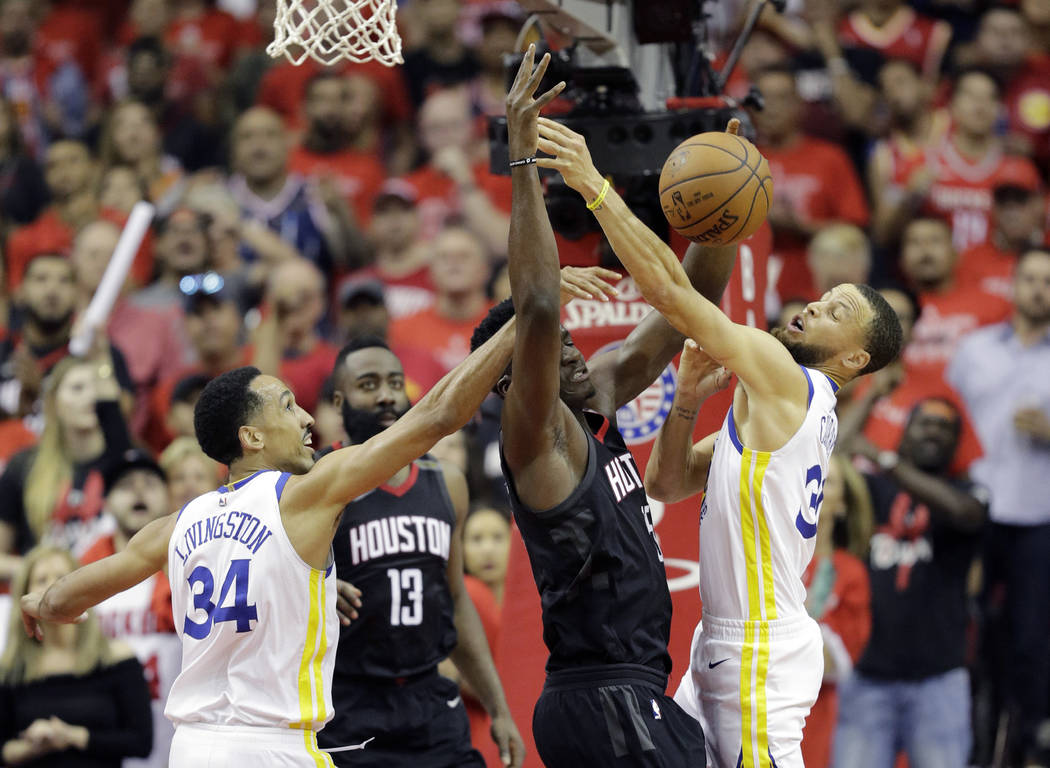 Houston Rockets center Clint Capela, center, is fouled by Golden State Warriors guard Stephen Curry, right, as he tries to score during the first half in Game 7 of the NBA basketball Western Confe ...