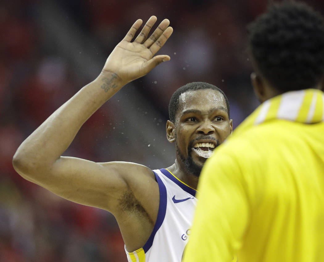 Golden State Warriors forward Kevin Durant, left, celebrates with teammates during the second half in Game 7 of the NBA basketball Western Conference finals against the Houston Rockets, Monday, Ma ...