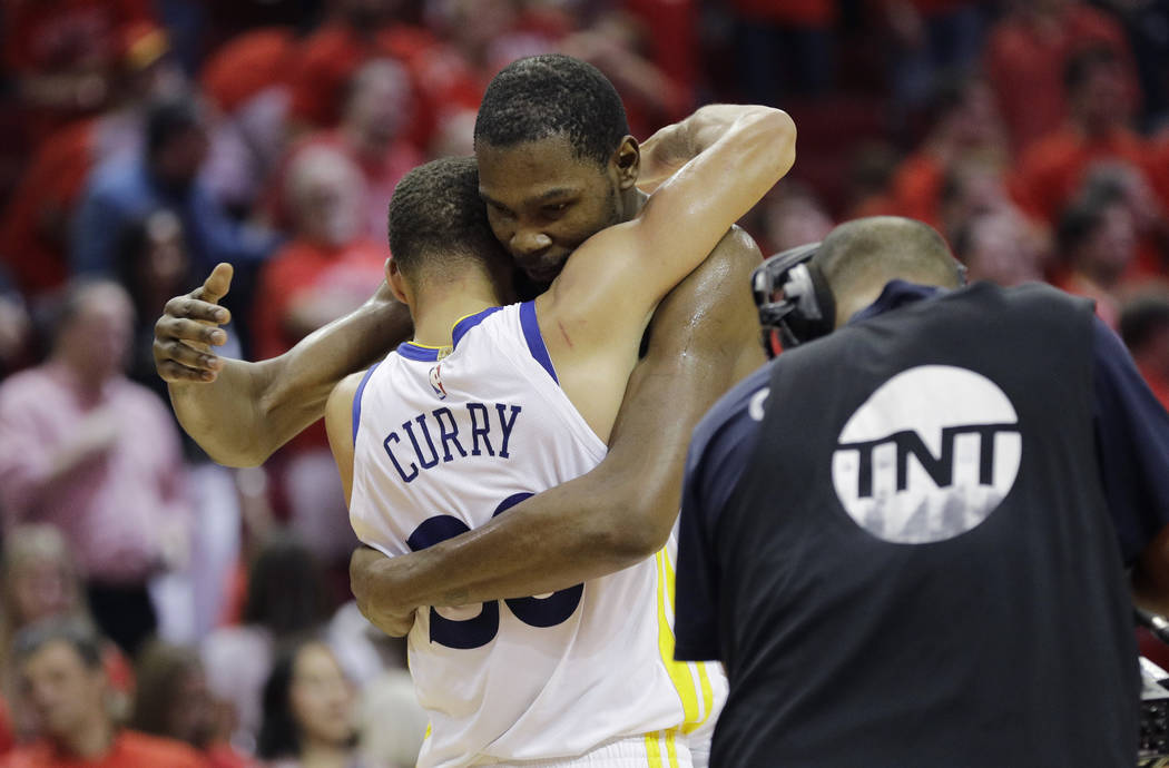 Golden State Warriors forward Kevin Durant, right, hugs teammate Stephen Curry, left, after they defeated the Houston Rockets in Game 7 of the NBA basketball Western Conference finals, Monday, May ...