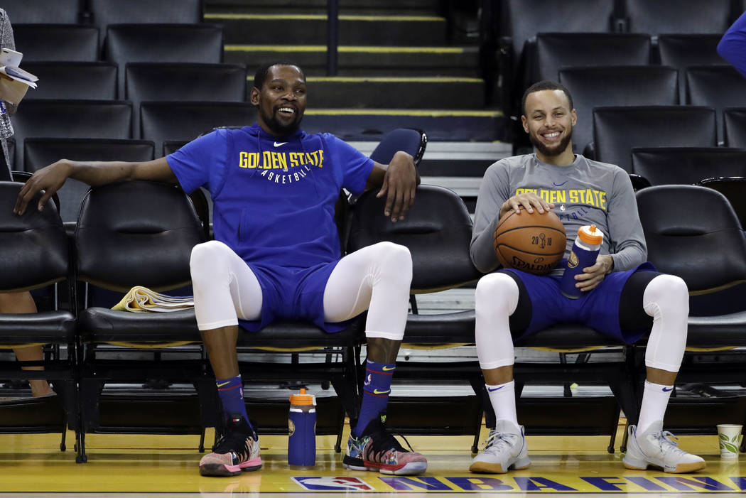 Golden State Warriors' Kevin Durant, left, and Stephen Curry smile as they take a break during an NBA basketball practice, Wednesday, May 30, 2018, in Oakland, Calif. The Warriors face the Clevela ...