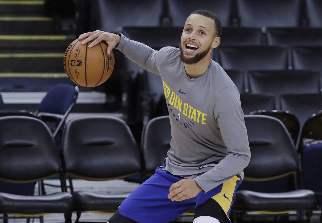 Golden State Warriors' Stephen Curry smiles as he dribbles during an NBA basketball practice, Wednesday, May 30, 2018, in Oakland, Calif. The Warriors face the Cleveland Cavaliers in Game 1 of the ...