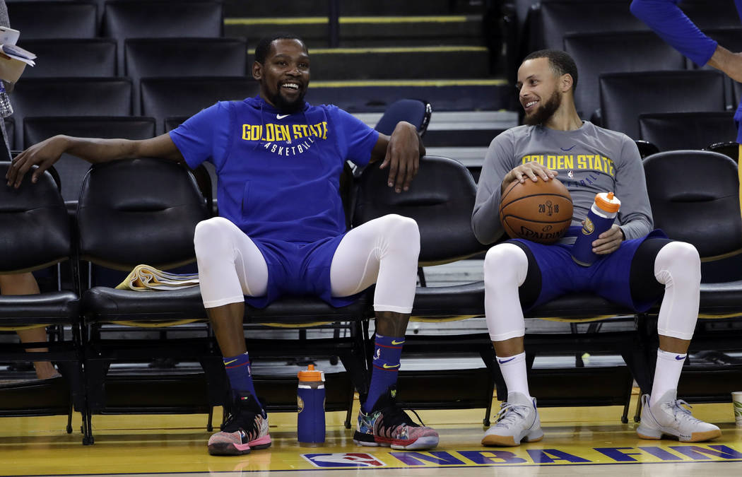 Golden State Warriors' Kevin Durant, left, smiles with teammate Stephen Curry during an NBA basketball practice, Wednesday, May 30, 2018, in Oakland, Calif. The Warriors face the Cleveland Cavalie ...