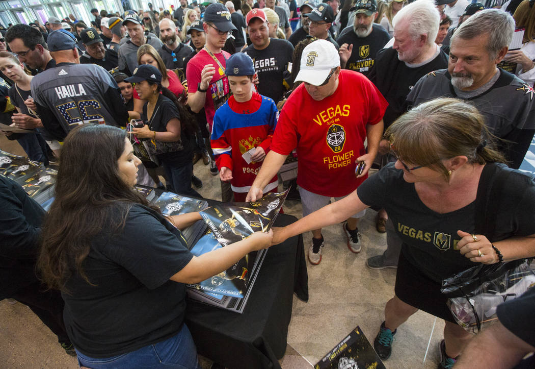 Fans pickup posters before the start of Game 2 of the NHL hockey Stanley Cup Final between the Golden Knights and Washington Capitals at the T-Mobile Arena in Las Vegas on Wednesday, May 30, 2018. ...