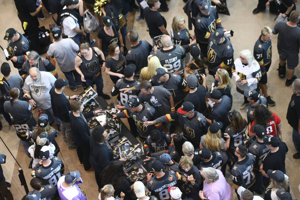 Fans get posters before the start of Game 2 of the NHL hockey Stanley Cup Final between the Golden Knights and Washington Capitals at the T-Mobile Arena in Las Vegas on Wednesday, May 30, 2018. Ch ...