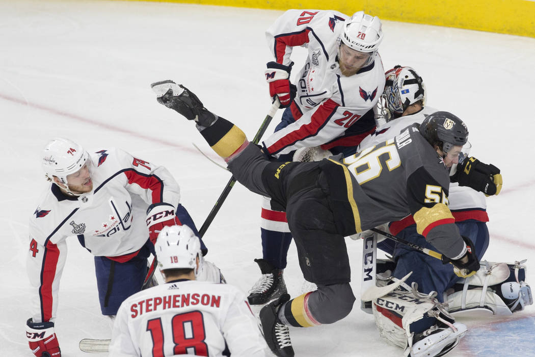 Golden Knights left wing Erik Haula (56) gets tripped up as Washington Capitals defenseman John Carlson (74), center Lars Eller (20) and goaltender Braden Holtby (70) defend during the first perio ...
