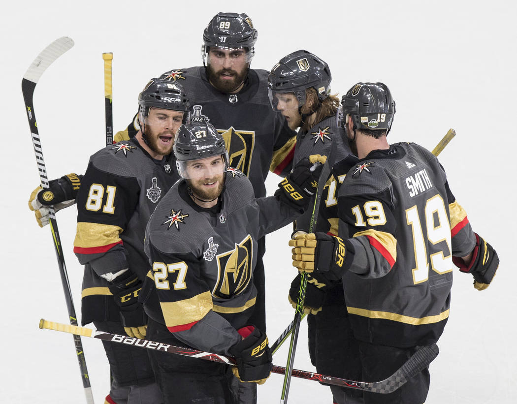 Golden Knights defenseman Shea Theodore (27) celebrates with teammates after scoring a second-period goal against the Washington Capitals during Game 2 of the NHL Stanley Cup Final on Wednesday, M ...