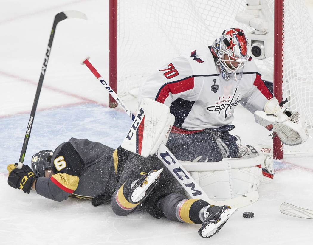 Capitals goaltender Braden Holtby (70) makes a third-period save against Golden Knights defenseman Colin Miller (6) during Game 2 of the NHL Stanley Cup Final on Wednesday, May 30, 2018, at T-Mobi ...