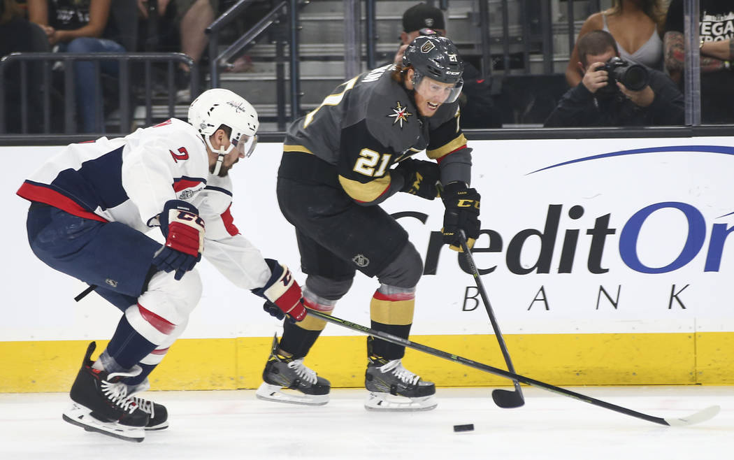 Golden Knights center Cody Eakin (21) sends the puck past Washington Capitals defenseman Matt Niskanen (2) during the first period of Game 2 of the NHL hockey Stanley Cup Final at the T-Mobile Are ...