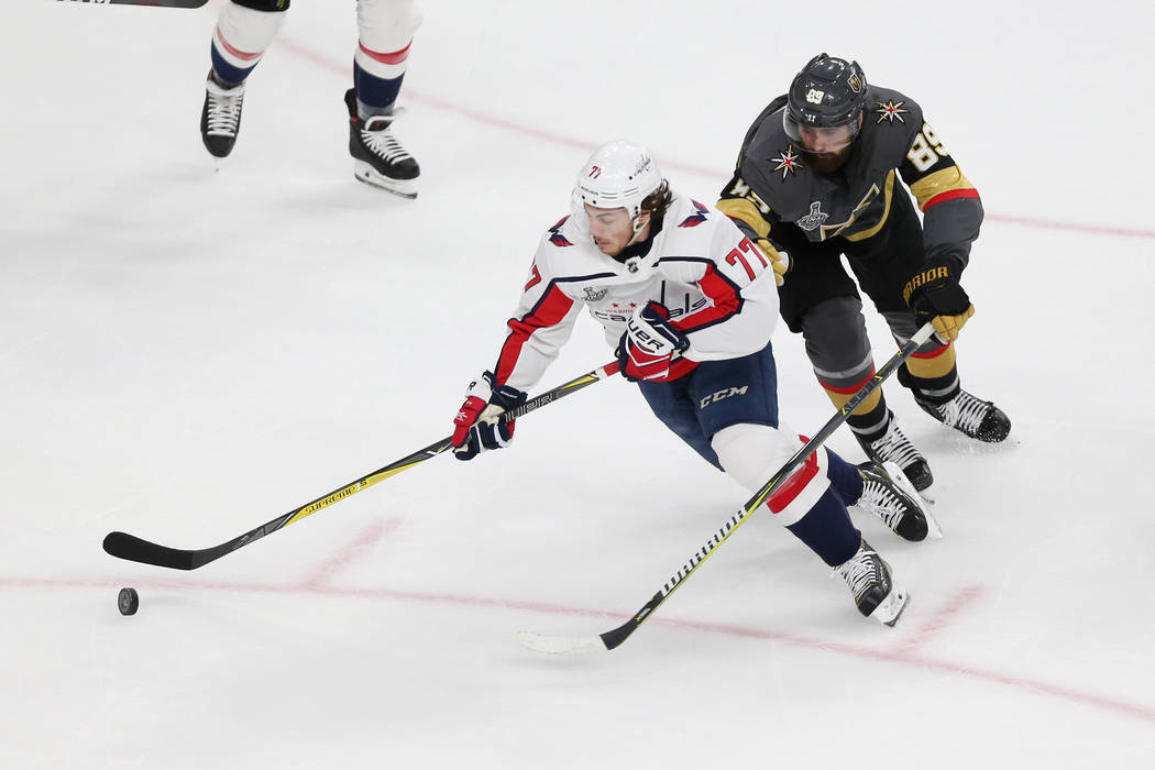 Washington Capitals right wing T.J. Oshie (77) and Vegas Golden Knights right wing Alex Tuch (89) go for the puck during the first period in Game 2 of the NHL hockey Stanley Cup Final at T-Mobile ...