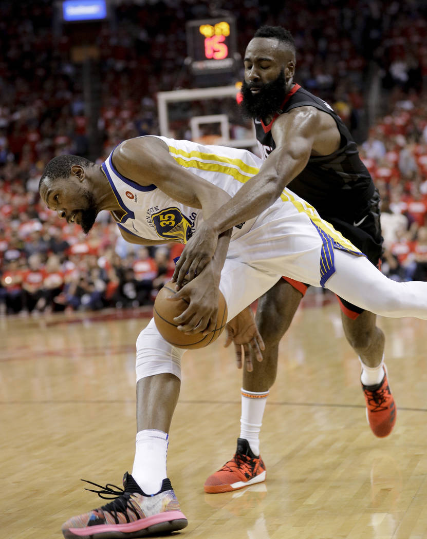 Houston Rockets guard James Harden, rear, fouls Golden State Warriors forward Kevin Durant during the first half in Game 5 of the NBA basketball playoffs Western Conference finals in Houston, Thur ...