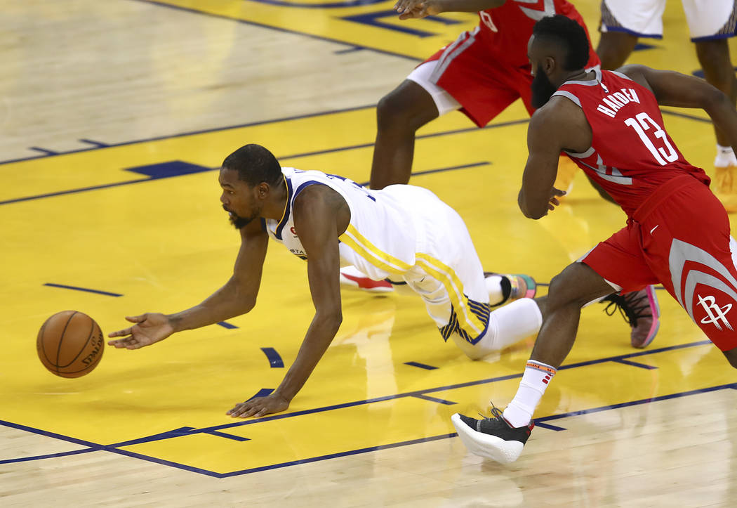Golden State Warriors forward Kevin Durant, left, reaches for the ball in front of Houston Rockets guard James Harden (13) during the second half of Game 6 of the NBA basketball Western Conference ...