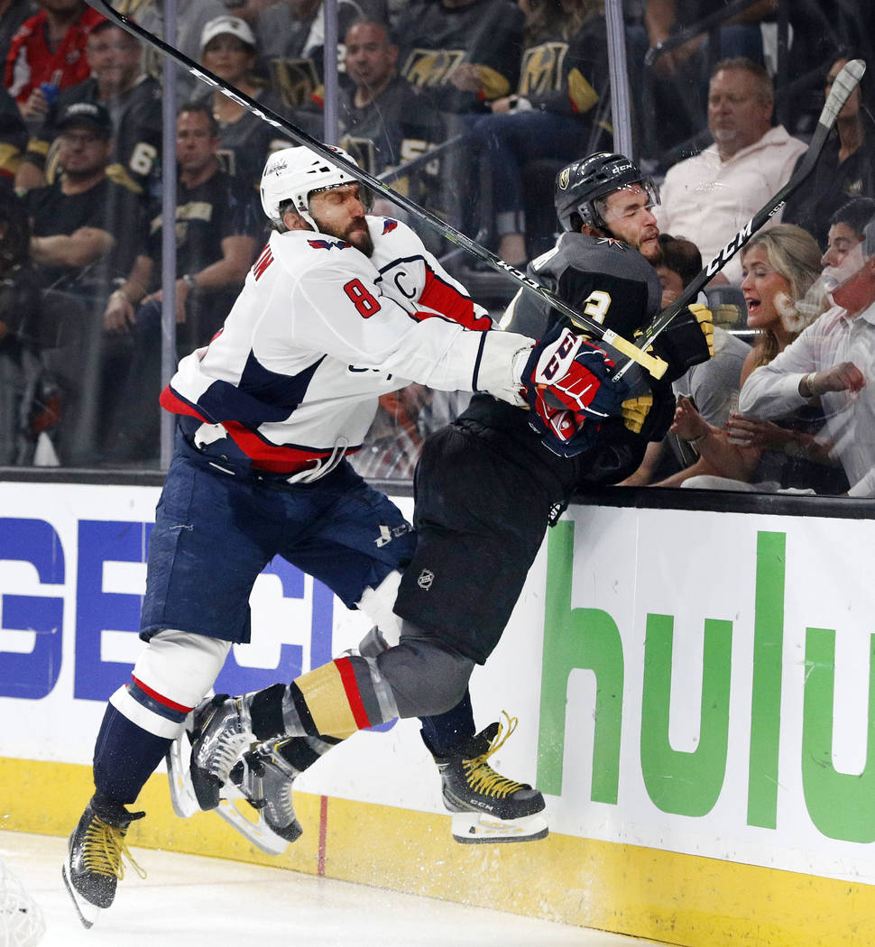 Washington Capitals left wing Alex Ovechkin, left, of Russia, puts Vegas Golden Knights defenseman Brayden McNabb into the boards during the first period in Game 2 of the NHL hockey Stanley Cup Fi ...