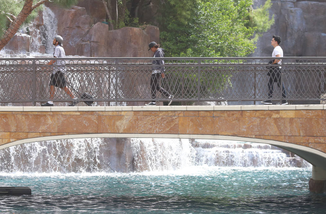 Tourists walk on the pedestrian bridge at Wynn hotel-casino during a hot day. (Bizuayehu Tesfaye/Las Vegas Review-Journal) @bizutesfaye