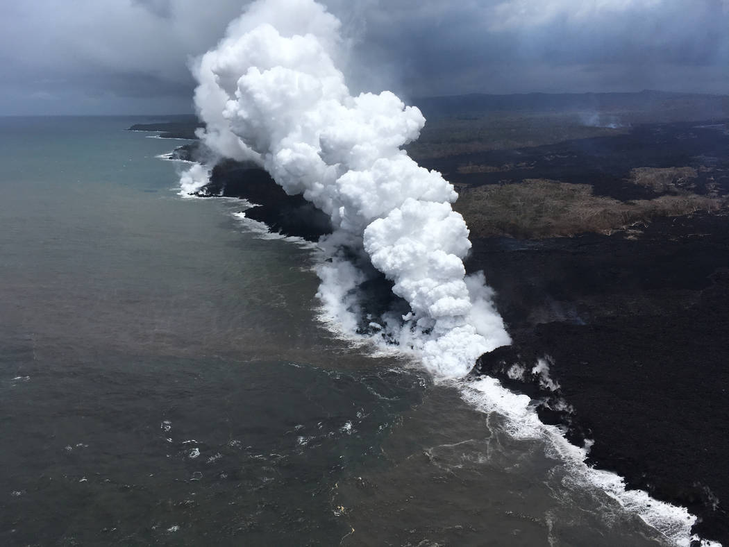 In this Saturday, May 26, 2018 image from video released by the U.S. Geological Survey, lava sends up clouds of steam and toxic gases as it enters the Pacific Ocean as Kilauea Volcano continues it ...