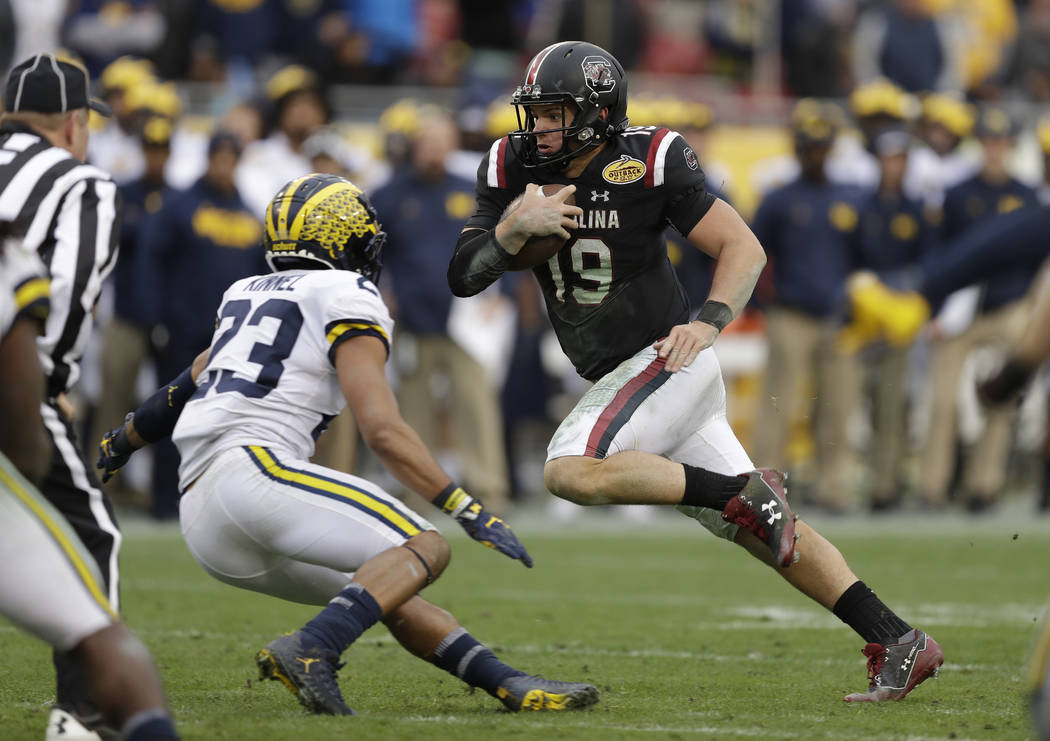 South Carolina quarterback Jake Bentley runs for yardage against Michigan during the second half of the Outback Bowl NCAA college football game Monday, Jan. 1, 2018, in Tampa, Fla. South Carolina ...