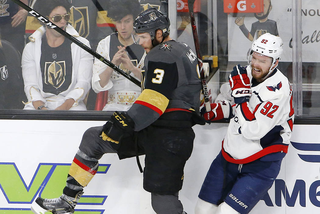 Washington Capitals center Evgeny Kuznetsov, right, of Russia, winces as he is checked by Vegas Golden Knights defenseman Brayden McNabb during the first period in Game 2 of the NHL hockey Stanley ...
