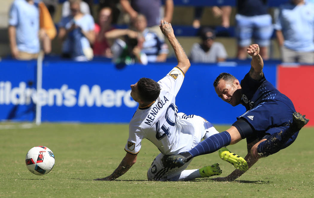 Sporting Kansas City midfielder Brad Davis, right, kicks the ball past Los Angeles Galaxy forward Raul Mendiola (40) during the first half of an MLS soccer match in Kansas City, Kan., Sunday, Sept ...